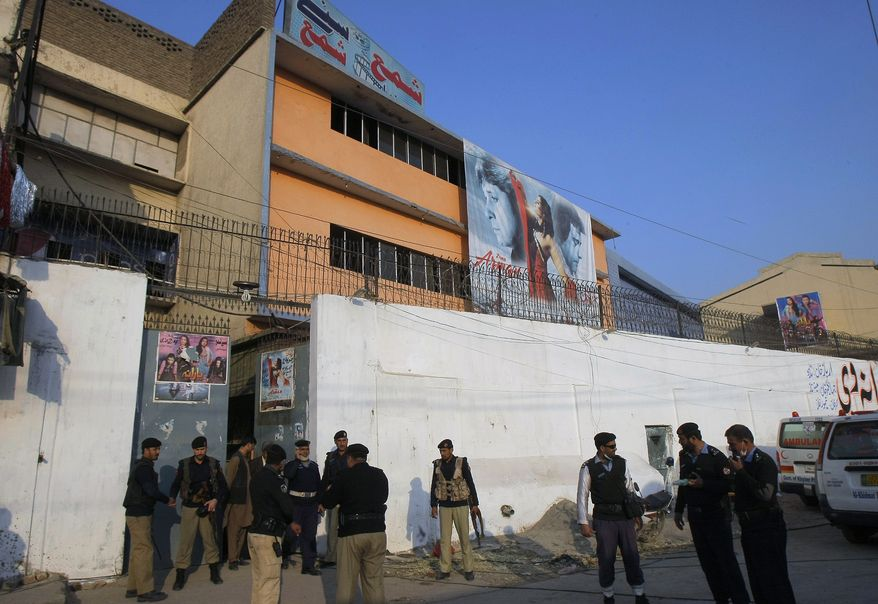 """Pakistani police officers gather outside a movie theater following a grenade attack that killed and wounded many people in Peshawar, Pakistan, Tuesday, Feb. 11, 2014. About 80 people were watching a movie called """"Yarana,"""" which means friendship in Pashto, said an official. No one immediately claimed responsibility for the attacks, which come days after Pakistan began a peace process with Taliban militants fighting in the country's northwest to end the violence that has killed more than 40,000 people in recent years. (AP Photo/Mohammad Sajjad)"""