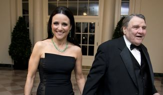 Actress Julia Louis-Dreyfus, left, arrives for a State Dinner in honor of French President François Hollande, with William Louis-Dreyfus at the White House in Washington, Tuesday, Feb. 11, 2014.   (AP Photo/Manuel Balce Ceneta)