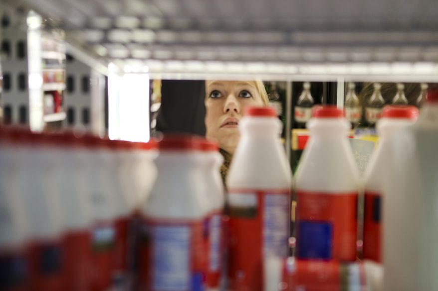 Jennifer Poulos reaches in the dairy shelves, Monday, Feb. 10, 2014, in Atlanta.On Monday, officials were quick to act as the winter weather zeroed in. Before a single drop of freezing rain or snow fell, Georgia Gov. Nathan Deal had declared a state of emergency for nearly a third of the state, schools canceled classes and workers were told to stay home. (AP Photo/Atlanta Journal-Constitution, John Spink)