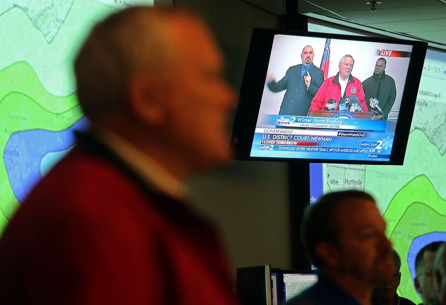 """Gov. Nathan Deal is shown on live TV while speaking at the GEMA command center, Tuesday, Feb. 11, 2014 in Atlanta. The city dodged the first punch of a dangerous winter storm Tuesday, but forecasters warned of a potentially """"catastrophic"""" second blow in the form of a thick layer of ice that threatened to bring hundreds of thousands of power outages and leave people in their cold, dark homes for days. (AP Photo/Atlanta Journal-Constitution, Ben Gray)  MARIETTA DAILY OUT; GWINNETT DAILY POST OUT; LOCAL TV OUT; WXIA-TV OUT; WGCL-TV OUT"""