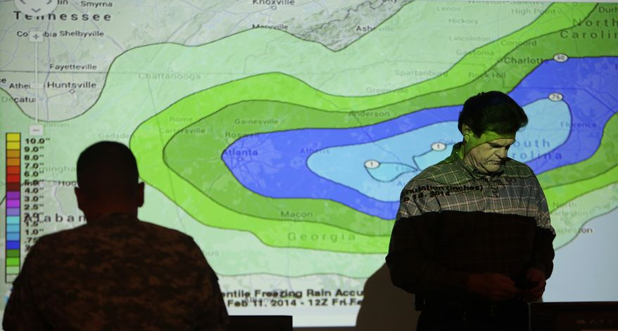 """Chuck Ray, right, Director of Field Operations for GEMA, walks through a projected map of possible ice accumulation while working in the GEMA command center, Tuesday, Feb. 11, 2014 in Atlanta. The city dodged the first punch of a dangerous winter storm Tuesday, but forecasters warned of a potentially """"catastrophic"""" second blow in the form of a thick layer of ice that threatened to bring hundreds of thousands of power outages and leave people in their cold, dark homes for days. (AP Photo/Atlanta Journal-Constitution, Ben Gray)  MARIETTA DAILY OUT; GWINNETT DAILY POST OUT; LOCAL TV OUT; WXIA-TV OUT; WGCL-TV OUT"""