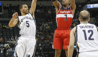 Washington Wizards guard Bradley Beal (3) shoots against Memphis forward Nick King (5) and guard Nick Calathes (12) in the first half of an NBA basketball game, Tuesday, Feb. 11, 2014, in Memphis, Tenn. (AP Photo/Lance Murphey)