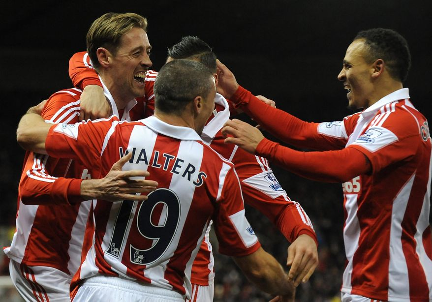 Stoke's Peter Crouch, left, celebrates with team mates after scoring against Swansea during the English Premier League soccer match between Stoke City and Swansea City at Britannia Stadium in Stoke On Trent, England, Wednesday, Feb. 12, 2014.  (AP Photo/Rui Vieira)