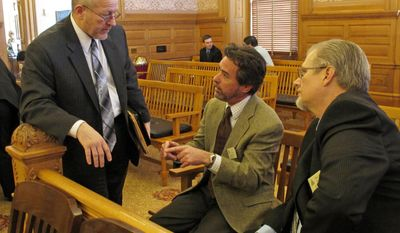 Kansas state Rep. Larry Campbell, left, an Olathe Republican, confers with Mike Taylor, center, a lobbyist for the Unified Government of Kansas City, Kan., and Wyandotte County, and Eric Smith, right, lobbyist for the League of Kansas Municipalities, after a committee meeting on gun-rights legislation, Wednesday, Feb. 12, 2014, at the Statehouse in Topeka, Kan. (AP Photo/John Hanna)