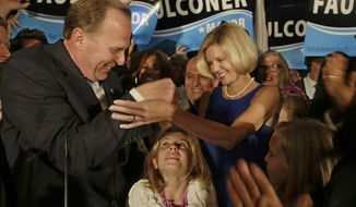 San Diego mayoral candidate Kevin Faulconer reaches for his wife, Katherine, as their daughter looks up from below after Faulconer addressed his supporters at a rally Tuesday, Feb. 11, 2014, in San Diego. (AP Photo/Lenny Ignelzi)