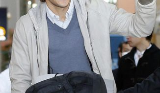 Uruguay striker Diego Forlan waves to supporters on his arrival at Kansai International Airport in Osaka, western Japan Wednesday, Feb. 12, 2014. Forlan will play for Cerezo Osaka in Japan. (AP Photo/Kyodo News) JAPAN OUT, MANDATORY CREDIT