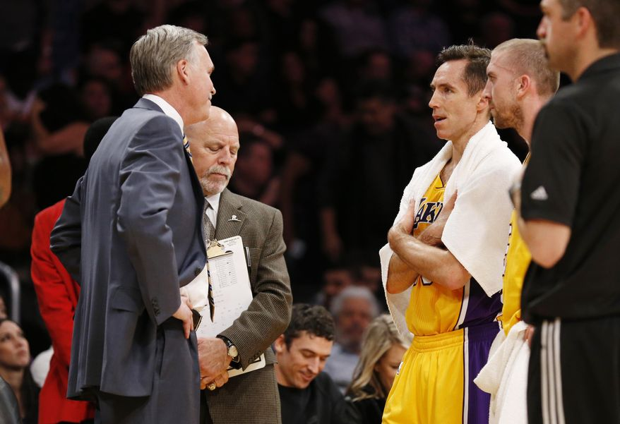 Los Angeles Lakers' Steve Nash, third from left, talks with coach Mike D'Antoni, left, as athletic trainer Gary Vitti, second from left, stands with them along with Steve Blake, right, while officials review a call at the end of the first half of an NBA basketball game against the Utah Jazz in Los Angeles, Tuesday, Feb. 11, 2014. (AP Photo/Danny Moloshok)