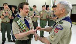 ** FILE ** In this Feb. 10, 2014, fie photo Pascal Tessier, left, a gay Boy Scout, receives his Eagle Scout badge from Troop 52 Scoutmaster Don Beckham, right, in Chevy Chase, Md., to become one of the first openly gay Scouts to reach scouting's highest rank. (AP Photo/Luis M. Alvarez, File)
