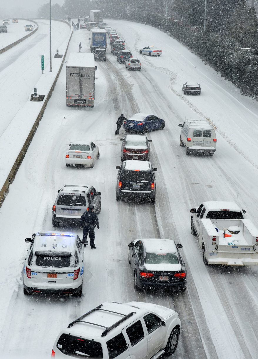 In the path of a storm: Traffic crawls along a slick roadway Wednesday in Charlotte, N.C. The winter storm that coated swaths of the South in ice and snow is poised to bring traffic problems and power outages to the D.C. region. Story, A12. (Associated Press photographs)