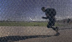 St. Louis Cardinals catcher Yadier Molina jogs along a fence during an informal spring training baseball practice Wednesday, Feb. 12, 2014, in Jupiter, Fla. Cardinals pitchers and catchers first official practice is scheduled for Thursday. (AP Photo/Jeff Roberson)