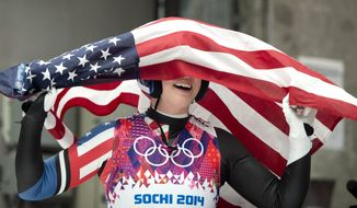 Erin Hamlin of the United States celebrates with the American flag after finishing her final run to win the bronze medal in the women's singles luge competition at the 2014 Winter Olympics, Tuesday, Feb. 11, 2014, in Krasnaya Polyana, Russia. (AP Photo/The Canadian Press, Jonathan Hayward)