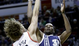 Oklahoma City Thunder forward Kevin Durant, right, shoots over Portland Trail Blazers center Robin Lopez during the first half of an NBA basketball game in Portland, Ore., Tuesday, Feb. 11, 2014. (AP Photo/Don Ryan)