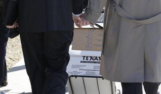 Victor Holmes, left, clutches the hand of partner Mark Phariss as they leave the U.S. Federal Courthouse, Wednesday, Feb. 12, 2014, in San Antonio. District Judge Orlando Garcia said Wednesday he would issue a decision later after the two Texas men filed a civil rights lawsuit seeking permission to marry, and a lesbian couple sued to have their marriage recognized. (AP Photo/Eric Gay)