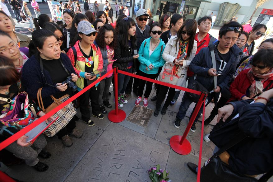 Chinese tourists take pictures at the hand and foot prints for Shirley Temple Black in front of the TCL Chinese Theatre in the Hollywood section of Los Angeles on Tuesday, Feb. 11, 2014. Temple, who died Monday night at 85, sang, danced, sobbed and grinned her way into the hearts of Depression-era moviegoers and remains the ultimate child star decades later. (AP Photo/Richard Vogel)