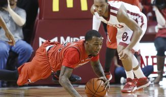 Texas Tech guard Jamal Williams, Jr. dives for a loose ball in front of Oklahoma guard Jordan Woodard during the first half on an NCAA college basketball game in Norman, Okla., Wednesday, Feb. 12, 2014. (AP Photo/Sue Ogrocki)