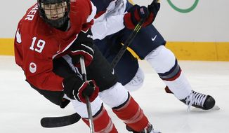 Meghan Duggan of the United States and Brianne Jenner of Canada races after the puck during the second period of the 2014 Winter Olympics women's ice hockey game at Shayba Arena, Wednesday, Feb. 12, 2014, in Sochi, Russia. (AP Photo/Petr David Josek)