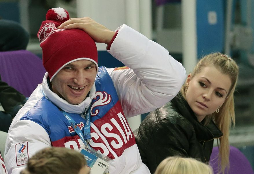 Russian ice hockey player Alexander Ovechkin, left, and retired Russian tennis player Maria Kirilenko attend the pairs short program figure skating competition at the Iceberg Skating Palace during the 2014 Winter Olympics, Tuesday, Feb. 11, 2014, in Sochi, Russia. (AP Photo/Ivan Sekretarev)