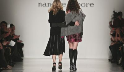 Fashion designer Nanette Lepore, left, walks the runway with her daughter, Violet, after showing her Fall 2014 collection during New York Fashion Week on Wednesday Feb. 12, 2014.  (AP Photo/Bebeto Matthews)