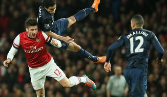 Arsenal's Olivier Giroud, left, falls after clashing with Manchester United's Rafael during their English Premier League soccer match between Arsenal and Manchester United at the Emirates stadium in London, Wednesday, Feb. 12, 2014. (AP Photo/Alastair Grant)