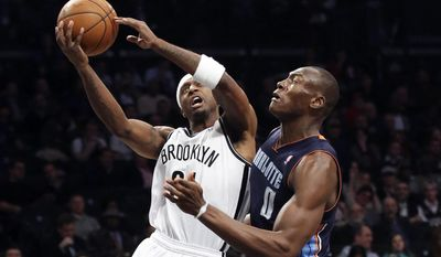Brooklyn Nets shooting guard Jason Terry, left, shoots against Charlotte Bobcats center Bismack Biyombo (0) in the first half of an NBA basketball game, Wednesday, Feb. 12, 2014, in New York. (AP Photo/John Minchillo)