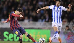 FC Barcelona's Lionel Messi of Argentina, left, kicks the ball in front Real Sociedad's Xabier Prieto, during their Spanish Copa del Rey semifinal second leg soccer match, at Anoeta stadium, in San Sebastian northern Spain, Wednesday, Feb. 12, 2014. (AP Photo/Alvaro Barrientos)