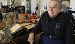 In this Feb. 7, 2014 photo, Lloyd Levin, 81, of Mount Prospect, Ill., sits at home with some of his collection of 3,000 antique Valentine's Day cards. Some predate the Civil War. (AP Photo/Daily Herald, Joe Lewnard)  MANDATORY CREDIT, MAGS OUT