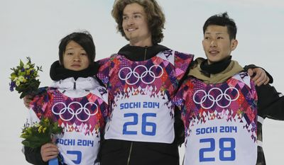 Switzerland's Iouri Podladtchikov celebrates on the podium with silver medalist  Ayumu Hirano of Japan, left, and bronze medalist  Taku Hiraoka, also of Japan, after he won the gold medal in the men's snowboard halfpipe final at the Rosa Khutor Extreme Park, at the 2014 Winter Olympics, Tuesday, Feb. 11, 2014, in Krasnaya Polyana, Russia.  (AP Photo/Andy Wong)