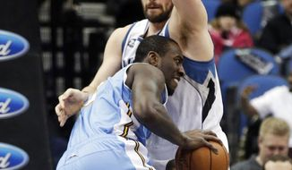 Denver Nuggets's J.J. Hickson, left, drives into Minnesota Timberwolves' Kevin Love in the first quarter of an NBA basketball game Wednesday, Feb. 12, 2014, in Minneapolis. (AP Photo/Jim Mone)