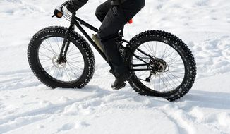 In this Feb. 6, 2014 photo, fat tire bicycle rider travels the trails at Jug Mountain Ranch near McCall, Idaho. Fat bikes sport oversized balloon tires run at low air pressures that are specially designed to ride on packed snow and other surfaces. (AP Photo/The Idaho Statesman, Roger Phillips)