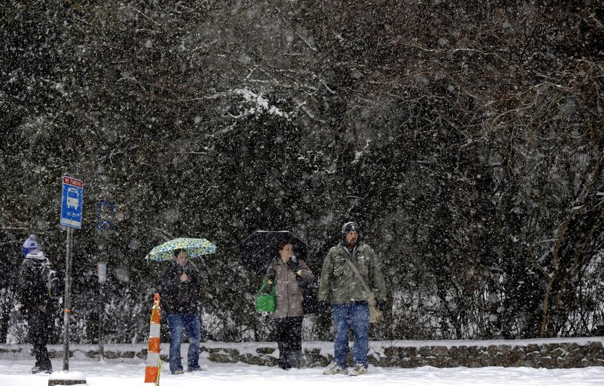 People wait in the falling snow at a bus stop in Chapel Hill, N.C., Wednesday, Feb. 12, 2014. The National Weather Service has issued a winter storm warning for Wednesday and into Thursday covering most of North Carolina. (AP Photo/Gerry Broome)