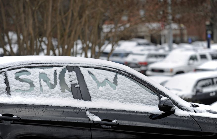 Snow covers a car on the University of Mississippi campus in Oxford, Miss., Tuesday, Feb. 11, 2014. (AP Photo/The Daily Mississippian, Thomas Graning)