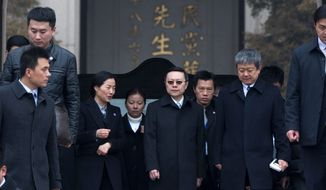 Wang Yu-chi (center wearing  sun glasses) head of Taiwan's Mainland Affairs Council, walks with other officials during his visit to the Mausoleum of Sun Yat-sen in Nanjing, Jiangsu province. (Associated Press)