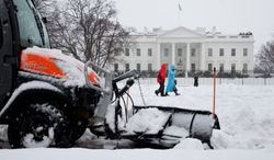 A plow removes snow from the sidewalk in Lafayette Park on Thursday as people make their way past the White House during D.C.'s  worst snowstorm in four years. (associated press)