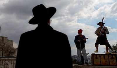 An ultra-Orthodox Jewish man looks at street performers as they play music near the Tower of David in Jerusalem's old city, Thursday, Feb. 6, 2014. (AP Photo/Sebastian Scheiner)