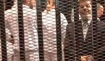 ** FILE ** Ousted President Mohammed Morsi, right, speakes from the defendant's cage as he stands with co-defendants in a makeshift courtroom during a trial hearing in Cairo, Egypt, Nov. 4, 2013. (AP Photo/Egyptian Interior Ministry, File)