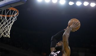 Miami Heat's LeBron James lays up a shot against the Golden State Warriors during the first half of an NBA basketball game on Wednesday, Feb. 12, 2014, in Oakland, Calif. (AP Photo/Ben Margot)