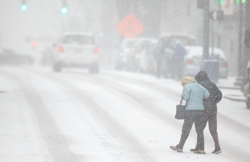 Pedestrians support each other as they cross S. Elm St. during a snow storm, Wednesday, Feb. 12, 2014 in Greensboro, N.C. As a third winter storm in as many days slammed into North Carolina, commutes that typically took minutes turned into hours-long ordeals. The National Weather Service issued a winter storm warning lasting into Thursday covering 95 of the state's 100 counties. (AP Photo/News & Record, Jerry Wolford)