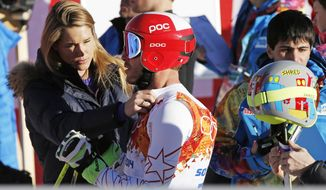 United States' Bode Miller has his ski bib adjusted by his wife Morgan Miller after completing men's downhill combined training at the Sochi 2014 Winter Olympics, Thursday, Feb. 13, 2014, in Krasnaya Polyana, Russia. (AP Photo/Christophe Ena)