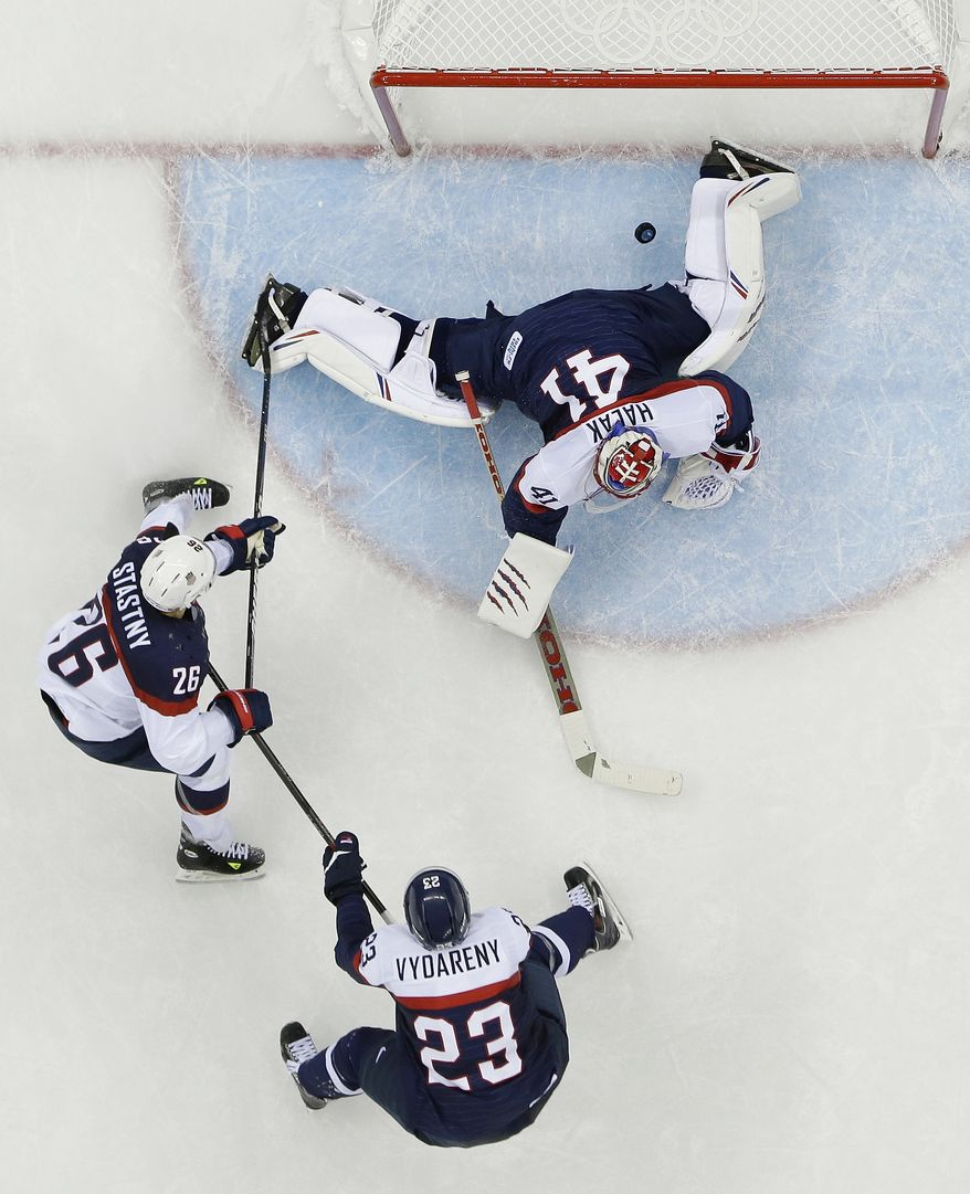 USA forward Paul Stastny (26) shoots past Slovakia goaltender Jaroslav Halak (41) for a goal as Slovakia defenseman Rene Vydareny (23) looks on during the 2014 Winter Olympics men's ice hockey game at Shayba Arena, Thursday, Feb. 13, 2014, in Sochi, Russia. (AP Photo/Matt Slocum)