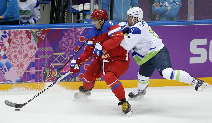 Russia forward Alexander Ovechkin, left, keeps the puck from Sovenia defenseman Matic Podlipnik in the first period of a men's ice hockey game at the 2014 Winter Olympics, Thursday, Feb. 13, 2014, in Sochi, Russia. (AP Photo/Mark Humphrey)