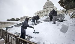 Workmen clear snow from the steps on Capitol Hill in Washington, Thursday, Feb. 13, 2014, as winter weather shut down Washington. After pummeling wide swaths of the South, a winter storm dumped nearly a foot of snow in Washington as it marched Northeast and threatened more power outages, traffic headaches and widespread closures for millions of residents. (AP Photo/J. Scott Applewhite)