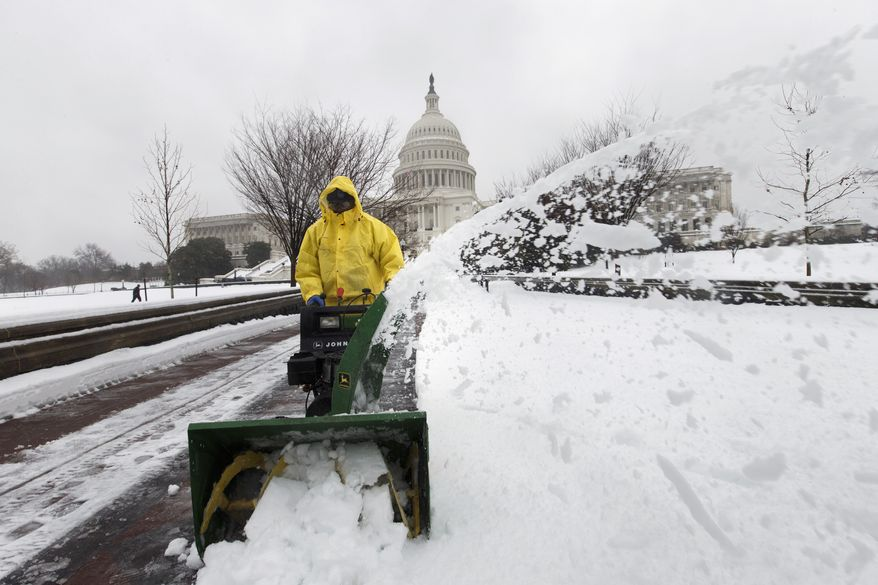 Workmen clear snow from around the Capitol as a winter storm shuts down Washington, Thursday, Feb. 13, 2014. After pummeling wide swaths of the South, a winter storm dumped nearly a foot of snow in Washington as it marched Northeast and threatened more power outages, traffic headaches and widespread closures for millions of residents. (AP Photo/J. Scott Applewhite)
