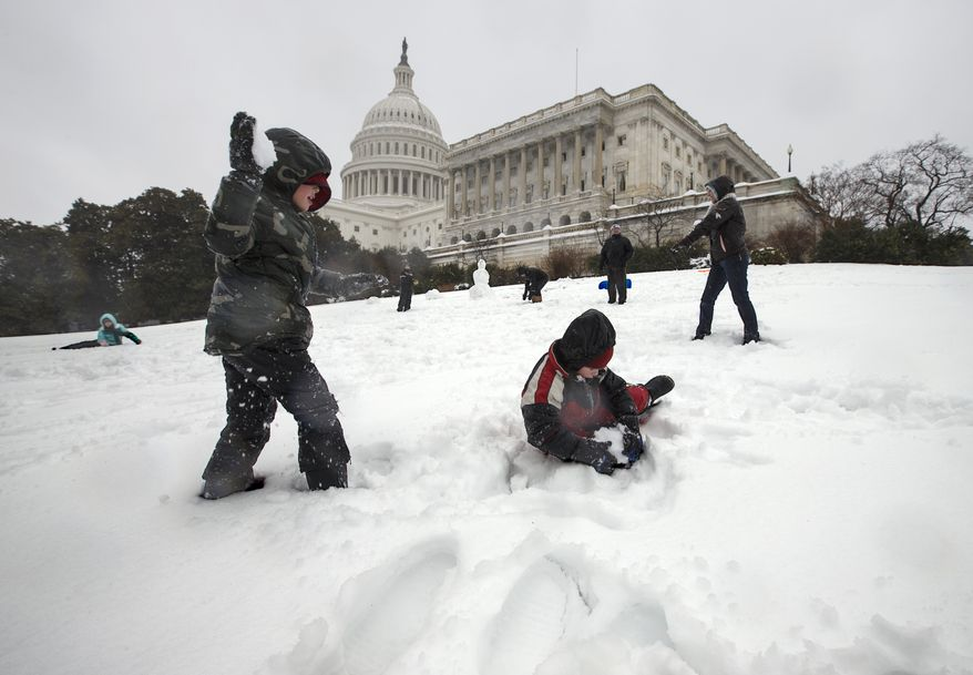 Children play in the snow on Capitol Hill in Washington, Thursday, Feb. 13, 2014, as winter weather shut down Washington. After pummeling wide swaths of the South, a winter storm dumped nearly a foot of snow in Washington as it marched Northeast and threatened more power outages, traffic headaches and widespread closures for millions of residents. (AP Photo/J. Scott Applewhite)