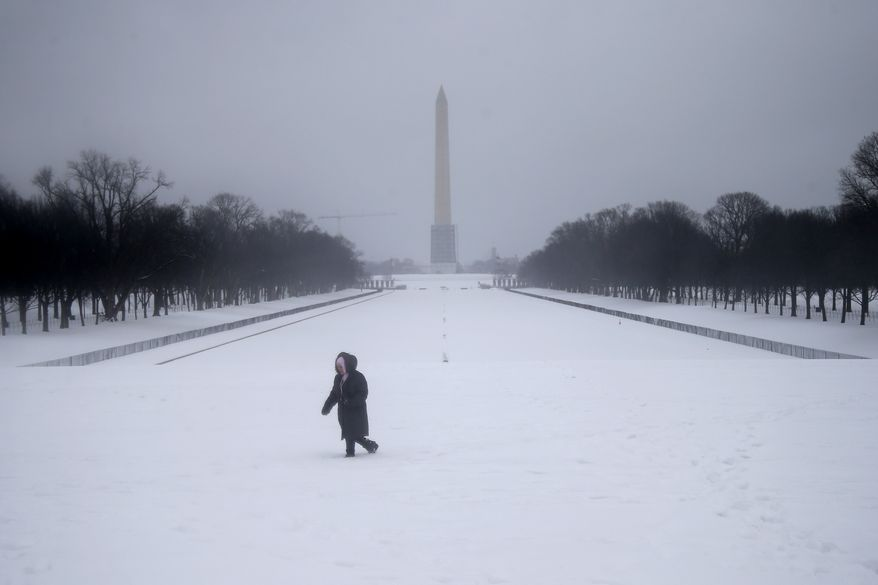 Maria Valero walks in the snow after taking photographs of the reflecting pool and the Washington Monument in Washington, Thursday, Feb. 13, 2014. After pummeling wide swaths of the South, a winter storm dumped nearly a foot of snow in Washington as it marched Northeast and threatened more power outages, traffic headaches and widespread closures for millions of residents. (AP Photo/Charles Dharapak)