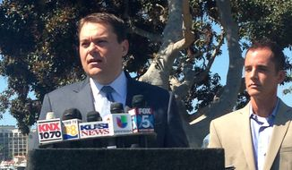 Carl DeMaio, left, a former city councilman who narrowly lost a bid for San Diego mayor last year, announces he won't seek the job again in a Nov. 19 special election to replace the disgraced Bob Filner in San Diego Calif., on Tuesday, Sept. 3, 2013. At his side in San Diego's Spanish Landing Park is partner Jonathan Hale. (AP Photo/ Elliot Spagat)