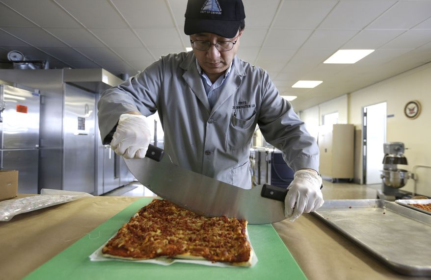 In this Thursday, Feb. 6, 2014 photo, food technologist Tom Yang cuts a prototype pizza at the U.S. Army Natick Soldier Research, Development and Engineering Center, in Natick, Mass. Pizza is in development to be used in individual field rations known as meal ready to eat, or MREs. It has been one of the most requested options for soldiers craving a slice of normalcy in the battlefield and disaster areas. (AP Photo/Steven Senne)