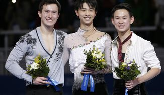 Yuzuru Hanyu of Japan, centre, Patrick Chan of Canada, left, and Denis Ten of Kazakhstan pose for photographs on the podium during the flower ceremony for the men's free skate figure skating final at the Iceberg Skating Palace during the 2014 Winter Olympics, Friday, Feb. 14, 2014, in Sochi, Russia. Hanyu placed first, Chan second and Ten third. (AP Photo/Bernat Armangue)