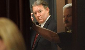 Michael Dunn leaves the courtroom after the verdict is read in Jacksonville, Fla. Saturday, Feb. 15, 2014. Dunn was convicted of attempted murder in the shooting death of a teenager during an argument over loud music, but jurors could not agree on the most serious charge of first-degree murder. (The Florida Times-Union, Bob Mack, Pool)