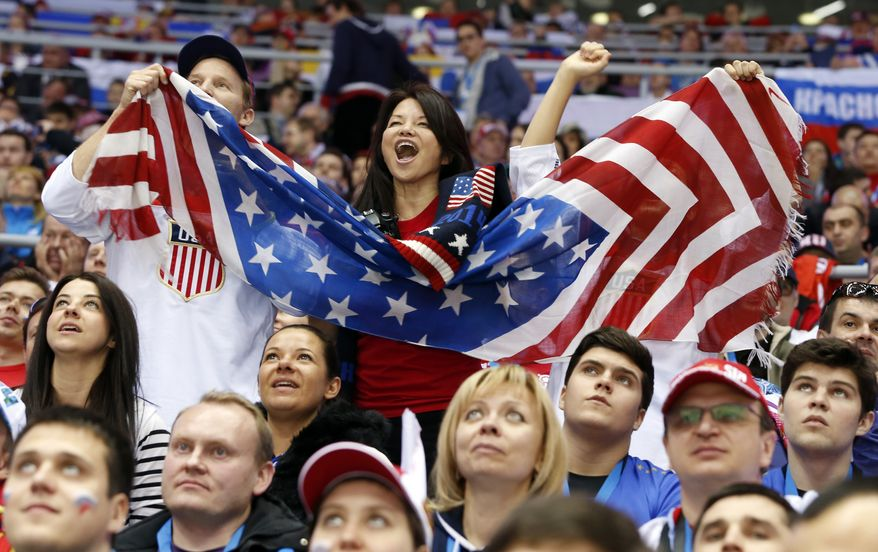 US fans cheer a second period goal by the USA against Russia during a men's ice hockey game at the 2014 Winter Olympics, Saturday, Feb. 15, 2014, in Sochi, Russia. (AP Photo/Mark Humphrey)
