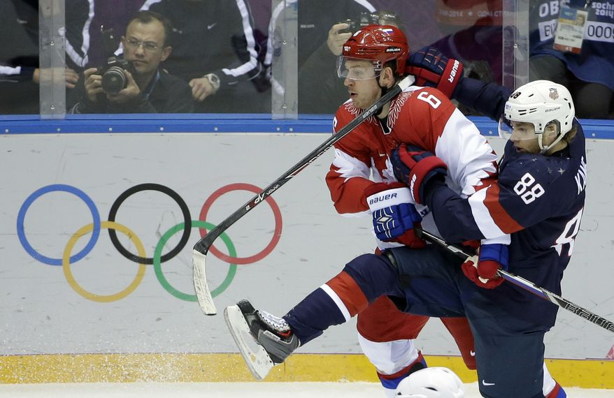 Russia defenseman Nikita Nikitin gets tangled up with USA forward Patrick Kane in the second period of a men's ice hockey game at the 2014 Winter Olympics, Saturday, Feb. 15, 2014, in Sochi, Russia. (AP Photo/David J. Phillip )
